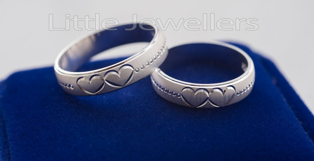 A heart embossed silver wedding rings