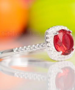 A captivating rich red halo design engagement ring