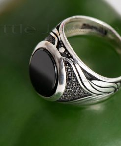 A sleek sterling silver men's ring that is uniquely detailed along the band.